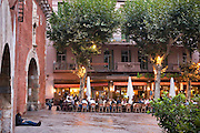 Festival participants who have been up all night partying gather at café shortly after dawn. Visa pour l'image International festival of photojournalism, held in Perpignan, France..