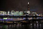Night scene looking over the River Thames towards the skyline of More London area offices and business district on 26th November 2019 in London, England, United Kingdom. More London, part of an area known as London Bridge City, is a development on the south bank of the Thames. It is owned by the Kuwaiti sovereign wealth fund. It includes office blocks, shops, restaurants, cafes, and a pedestrianised area. In the foreground is the Thames Clipper stop at Tower Millennium Pier.