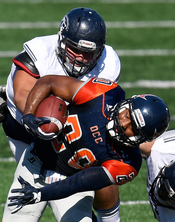 Orange Coast College's Derrick Hunt, front, grips the ball as Fullerton College's Domonic Sanchez tries to knock the ball out of his hand during the Orange Coast College vs. Fullerton College football game at Orange Coast College in California on Saturday.