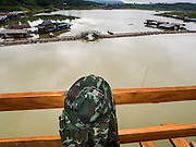 16 SEPTEMBER 2014 - SANGKHLA BURI, KANCHANABURI, THAILAND: A Thai soldier's uniform hangs on the safety rail of the Mon Bridge, the temporary bamboo bridge being used while the Mon Bridge is repaired is in the background. The 2800 foot long (850 meters) Saphan Mon (Mon Bridge) spans the Song Kalia River. It is reportedly second longest wooden bridge in the world. The bridge was severely damaged during heavy rainfall in July 2013 when its 230 foot middle section  (70 meters) collapsed during flooding. Officially known as Uttamanusorn Bridge, the bridge has been used by people in Sangkhla Buri (also known as Sangkhlaburi) for 20 years. The bridge was was conceived by Luang Pho Uttama, the late abbot of of Wat Wang Wiwekaram, and was built by hand by Mon refugees from Myanmar (then Burma). The wooden bridge is one of the leading tourist attractions in Kanchanaburi province. The loss of the bridge has hurt the economy of the Mon community opposite Sangkhla Buri. The repair has taken far longer than expected. Thai Prime Minister General Prayuth Chan-ocha ordered an engineer unit of the Royal Thai Army to help the local Mon population repair the bridge. Local people said they hope the bridge is repaired by the end November, which is when the tourist season starts.    PHOTO BY JACK KURTZ