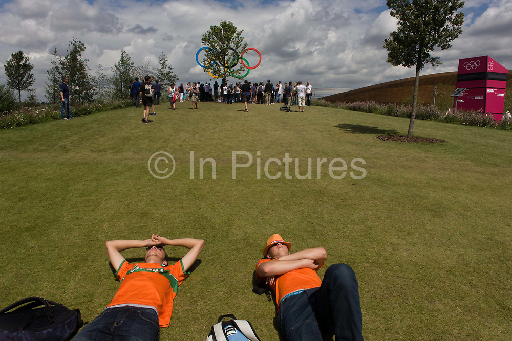 Dutch spectators rest on the grass near giant Olympic rings located on a hill in the Olympic Park during the London 2012 Olympics. This land was transformed to become a 2.5 Sq Km sporting complex, once industrial businesses and now the venue of eight venues including the main arena, Aquatics Centre and Velodrome plus the athletes' Olympic Village. After the Olympics, the park is to be known as Queen Elizabeth Olympic Park.