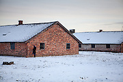 A young visitor is praying outside of one of the brick barracks which had been the first buildings for prisoners constructed at the Auschwitz II-Birkenau camp. In the BI section 30 such barracks were errected in total.
