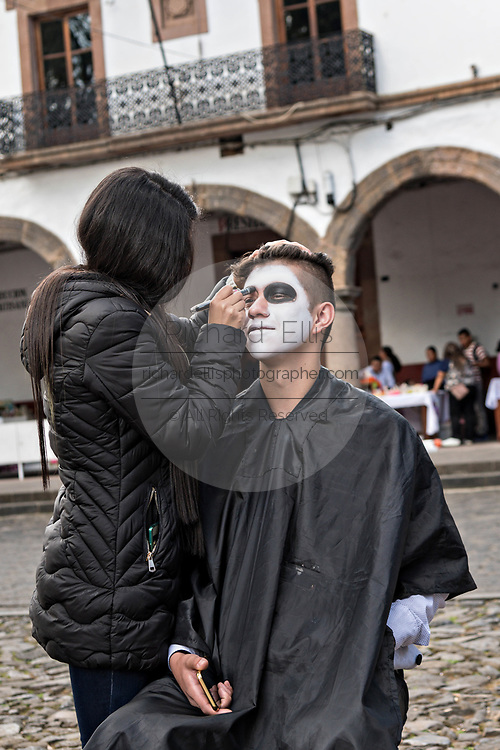 A young man has face paint applied during the Day of the Dead or Día de Muertos festival October 31, 2017 in Patzcuaro, Michoacan, Mexico. The festival has been celebrated since the Aztec empire celebrates ancestors and deceased loved ones.