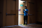"""Anthony """"Rumble"""" Johnson checks his phone backstage before the official UFC 187 weigh-in event at the MGM Grand in Las Vegas, Nevada on May 22, 2015. (Cooper Neill)"""