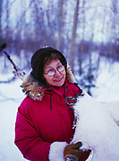 Jeannie Stevens holding traditional brain-tanned moose hide that has recently been scraped, Bettles, Alaska.