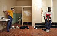 """J.V. Martin Junior High School seventh graders, Johnathan Jacobs, 14, and Danell Thompson, 13, joke around as they change clothes in the locker room after gym class. Concerning the condition of the locker room Jacobs said, """"It's just wrong… it stinks in here"""" The locker room has no heat, lockers, or a place to change in private."""