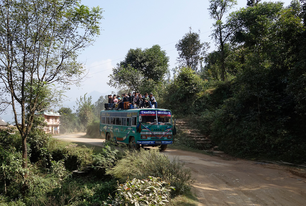 Passengers riding on the roof of a bus in the Gorkha region of Nepal.