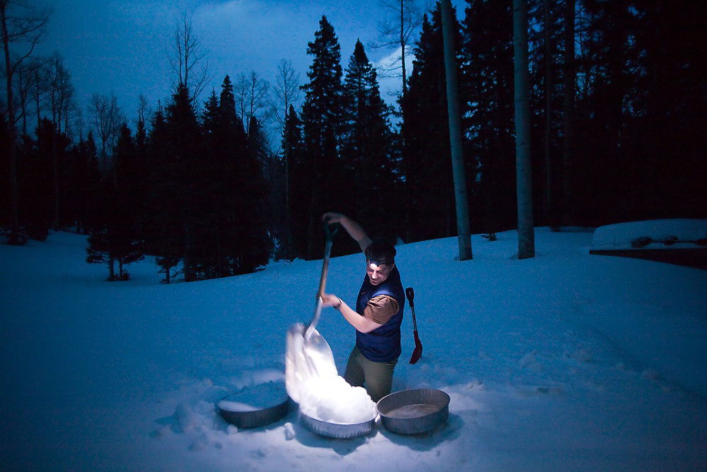 Judd MacRae shovels snow into melting pans for drinking water outside the backcountry North Pole Hut, San Juan Mountains, Colorado.