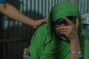 """Relatives try to console Maksuda after she heard the death news of her friend Najma Begum.Najma Begum called her friend Maksuda before she died. She was very<br /> sick and saying"""" Please save me, I am going to die, they are killing me."""" Najma went<br /> to Saudi Arabia to work with a house visa. Manikganj, Bangladesh,2019"""