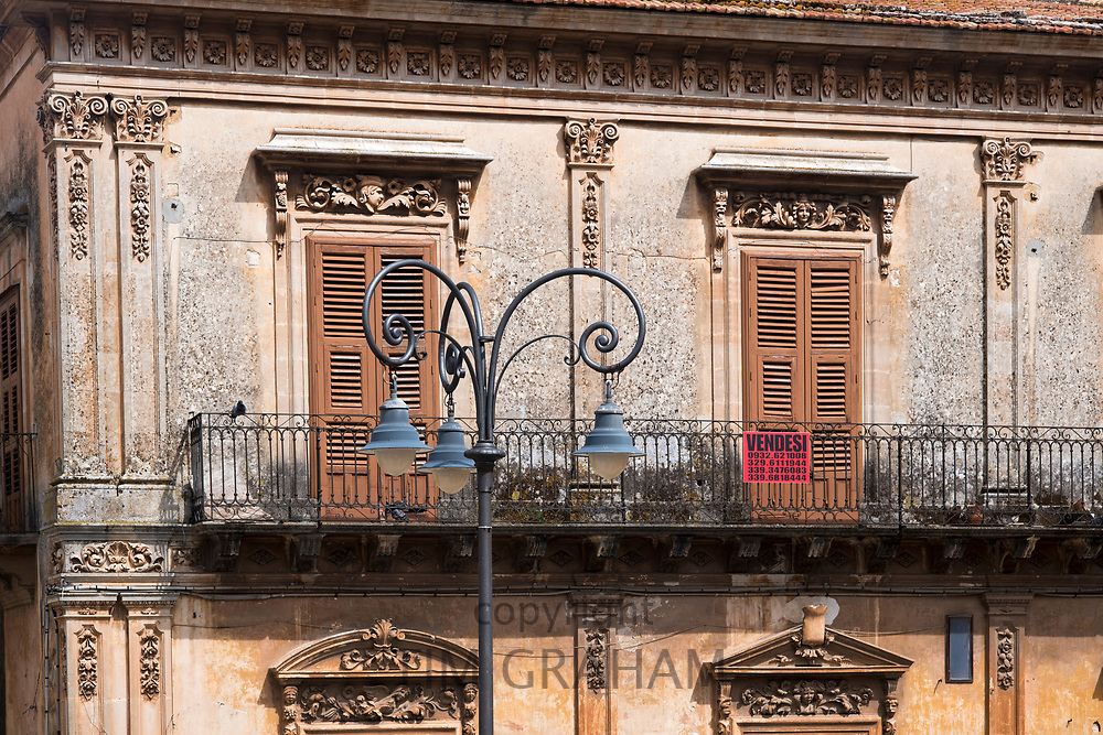 Typical traditional Sicilian architecture balcony, shutters and ornate stonework in Piazza San Giovanni in Ragusa Ibla, Sicily