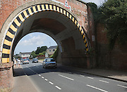 Warning paint over arch of low road bridge in Lawford, near Manningtree, Essex, England
