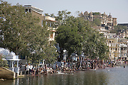 Men at the bathing ghats washing off paint powder after the festival of Holi. Lake Pichola, Udaipur, Rajasthan, India.