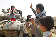 Mcc0030300 . Sunday Telegraph..Jubilant Libyans pose for pictures on destroyed Libyan Army T72 tank in the town of Ajdabiyah after Libyan government forces retreated on saturday night due to repeated attacks from NATO airstrikes...Ajdabiyah 26 March 2011