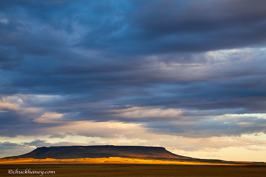 Morning sunlight breaks through the cloud cover and illuminates Square Butte near Great Falls, Montana, USA