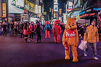 Costumed characters and holiday shoppers walk thru Time Square