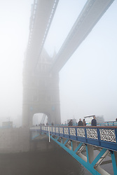 © Licensed to London News Pictures. 12/12/2012. London, UK. People and traffic cross Tower Bridge in London during thick freezing fog this morning, 12 December 2012. Photo credit : Vickie Flores/LNP.