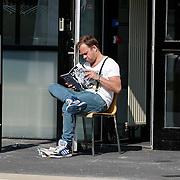 NLD/Hilversum/20130505 - Carlo Boszhard geniet van de lentezon en leest in de biografie van Patricia Paay
