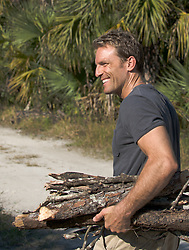 All American man carrying wood outdoors
