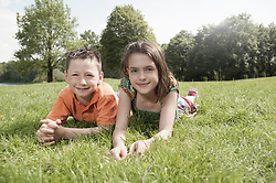 Two friends lying on grass in a park, Munich, Bavaria, Germany