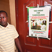 INDIVIDUAL(S) PHOTOGRAPHED: Sola Oyesemmi. LOCATION: Ikeja Primary Health Care Center, Lagos, Nigeria. CAPTION: Sola Oyesemmi stands next to an information poster about tuberculosis that hangs in one of the corridors at the Ikeja Health Center.