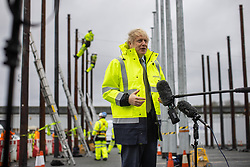© Licensed to London News Pictures. 18/12/2020. Manchester, UK. British Prime Minister BORIS JOHNSON stands in front of a pool TV camera as trainee engineers climb telephone poles behind him , during a visit the Open Reach Bolton Training Centre in Bolton . Photo credit: Joel Goodman/LNP