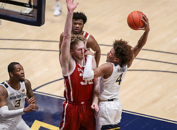 Feb 13, 2021; Morgantown, West Virginia, USA; West Virginia Mountaineers guard Miles McBride (4) drives and shoots against Oklahoma Sooners forward Brady Manek (35) during the second half at WVU Coliseum. Mandatory Credit: Ben Queen-USA TODAY Sports