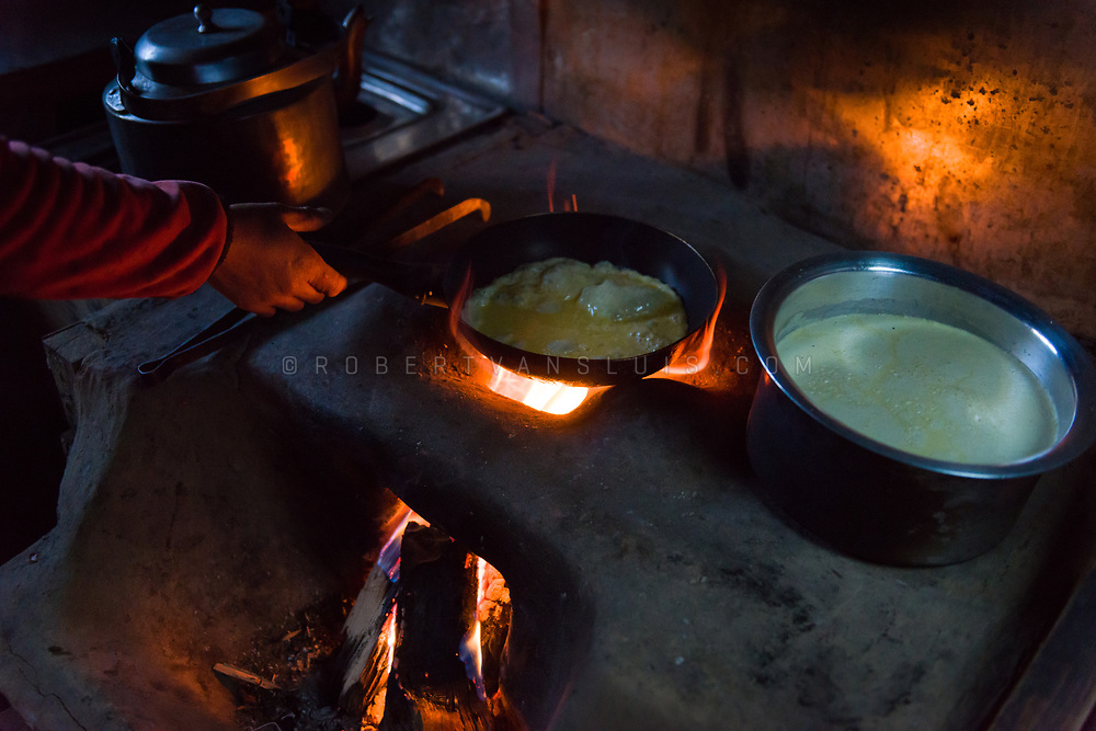 A woman cooks an omelette in a lodge in the Nepal Himalaya. Photo © robertvansluis.com