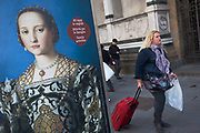 A modern Italian woman walks past Agnolo de Cosimo Bronzino's painting of the Medici Eleanora of Toledo and son Giovanni C1545. The poster advertises the art exhibition by the celebrated painter Agnolo de Cosimo Bronzino. Agnolo de Cosimo Bronzino's painting of the Medici Eleanora of Toledo and son Giovanni C1545. Eleonora di Toledo (1522 – 1562), the daughter of Don Pedro Álvarez de Toledo, the Spanish viceroy of Naples. Eleonora was a patron of the new Jesuit order, and her private chapel in the Palazzo Vecchio  was decorated by Bronzino, who had originally arrived in Florence to provide festive decor for her wedding. She died, with her sons Giovanni and Garzia, in 1562, when she was only forty; all three of them were struck down by malaria while traveling to Pisa.