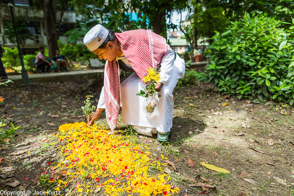 """08 AUGUST 2013 - BANGKOK, THAILAND: A man tends to his wife's grave in the Muslim cemetery next to Haroon Mosque after Eid al-Fitr services in Bangkok. Tending graves is a tradition on Eid. Eid al-Fitr is the """"festival of breaking of the fast,"""" it's also called the Lesser Eid. It's an important religious holiday celebrated by Muslims worldwide that marks the end of Ramadan, the Islamic holy month of fasting. The religious Eid is a single day and Muslims are not permitted to fast that day. The holiday celebrates the conclusion of the 29 or 30 days of dawn-to-sunset fasting during the entire month of Ramadan. This is a day when Muslims around the world show a common goal of unity. The date for the start of any lunar Hijri month varies based on the observation of new moon by local religious authorities, so the exact day of celebration varies by locality.      PHOTO BY JACK KURTZ"""