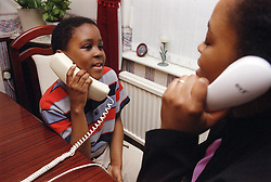 Social worker with young boy using the telephone,