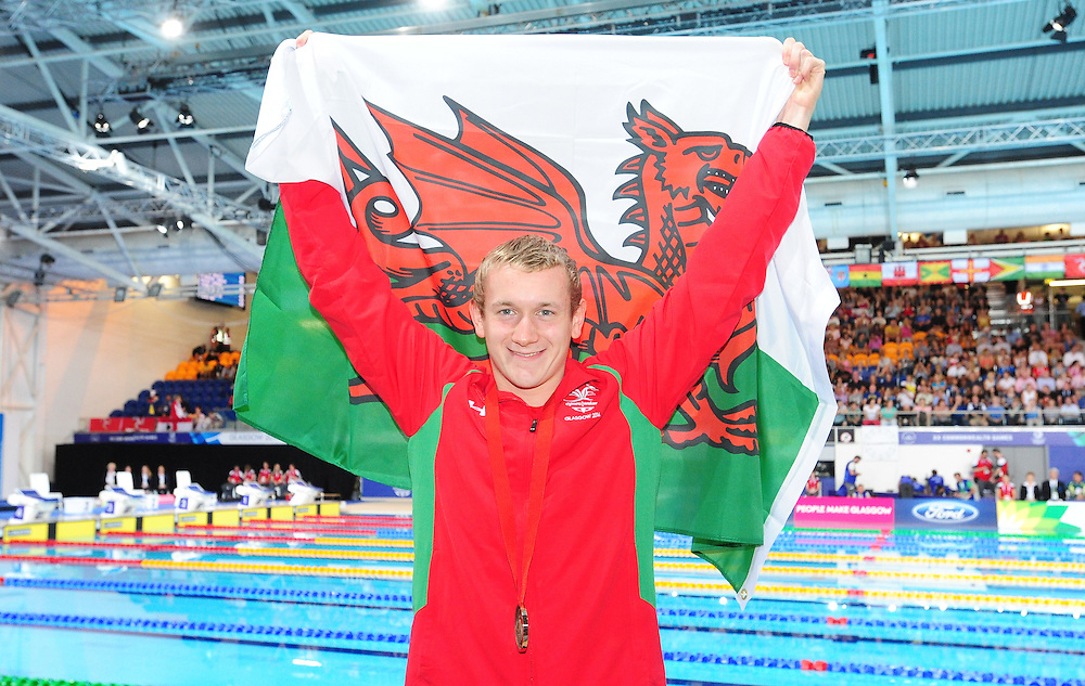 Wales' Jack Thomas poses with the Welsh flag after taking the bronze medal in the men's para-sport 200m freestyle S14 final<br /> <br /> Photographer Chris Vaughan/CameraSport<br /> <br /> 20th Commonwealth Games - Day 3 - Saturday 26th July 2014 - Swimming - Tollcross International Swimming Centre - Glasgow - UK<br /> <br /> © CameraSport - 43 Linden Ave. Countesthorpe. Leicester. England. LE8 5PG - Tel: +44 (0) 116 277 4147 - admin@camerasport.com - www.camerasport.com