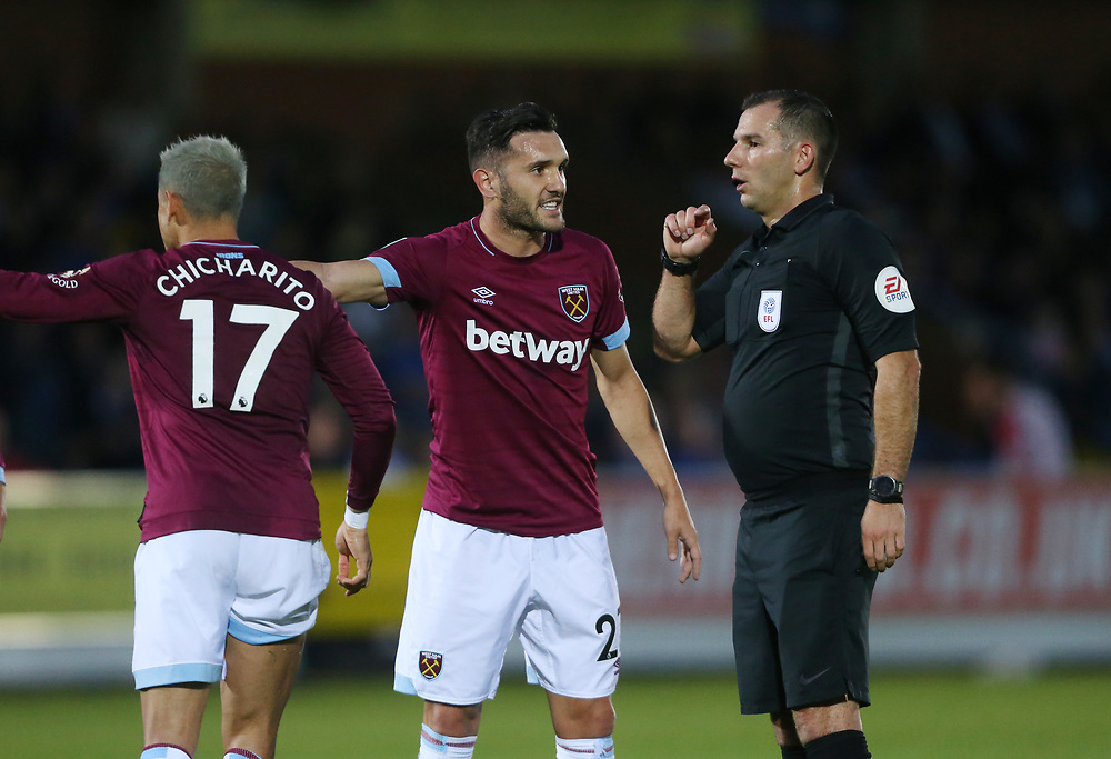 West Ham United's Lucas Perez makes a point to referee Tim Robinson<br /> <br /> Photographer Rob Newell/CameraSport<br /> <br /> The Carabao Cup Second Round - AFC Wimbledon v West Ham United - Tuesday 28 August 2018 - Kingsmeadow - London<br />  <br /> World Copyright © 2018 CameraSport. All rights reserved. 43 Linden Ave. Countesthorpe. Leicester. England. LE8 5PG - Tel: +44 (0) 116 277 4147 - admin@camerasport.com - www.camerasport.com