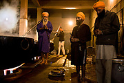 Cooks at the Golden Temple's Langar, begin the day in prayer before they start the intense day's activities of prepariing food for thousands of pilgrims which will visit the holiest of Gudwara's of the Sikh religion, Amritsar, Punjab, India.