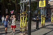A tour leader holdds up a Union Jack flag on a busy street corner with yellow scaffolding protection sleeves and passing pedestrians on Long Acre near Covent Garden, on 1st September 2017, in London, England.
