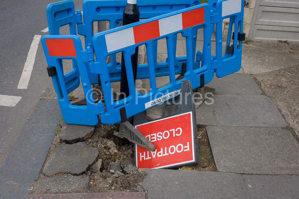 A Closed Footpath sign fallen into a hole during pavement works in the south London borough of Lewisham. A blue plastic barrier inexpertly blocks the broken paving stones at a pedestrian crossing in Brockley in south London. And we notice the upside down sign telling the public that the pathway is closed, dangerous to use and evidence of disruption to the inform or users of wheelchairs or childrens' buggies. Comically, the notice is itself, falling down the hole.
