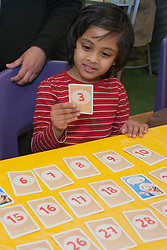 United States, Washington, Bellevue, KidsQuest Children's Museum,girl playing math game at family math night with Explorations in Math