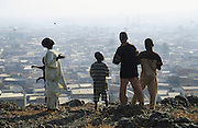 Husa Muslim youths on Dala Hill, in the centre of Kano, a mountain of rocks around which the city was built, the rocky outcrop is very important sacred Animist place..The implementation of Islamic Sharia Law across the twelve northern states of Nigeria, centres upon Kano, the largest Muslim Husa city, under the feudal, political and economic rule of the Emir of Kano. Islamic Sharia Law is enforced by official state apparatus including military and police, Islamic schools and education, plus various volunteer Militia groups supported financially and politically by the Emir and other business and political bodies. Fanatical Islamic Sharia religious traditions  are enforced by the Hispah Sharia police. Deliquancy is controlled by the Vigilantes volunteer Militia. Activities such as Animist Pagan Voodoo ceremonies, playing music, drinking and gambling, normally outlawed under Sharia law exist as many parts of the rural and urban areas are controlled by local Mafia, ghetto gangs and rural hunters. The fight for control is never ending between the Emir, government forces, the Mafia and independent militias and gangs. This is fueled by rising petrol costs, and that 70% of the population live below the poverty line. Kano, Kano State, Northern Nigeria, Africa