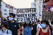 """A protester hold a banner reading """"The victims were no foreign"""" as people take part in a memorial demonstration to the victims of the Hanau terror attack, in Berlin, Germany, August 19, 2020. Thousands of protesters marched through the German capital's Neuköln district in remembrance of the Hanau shootings, in which ten people were killed and five others wounded. The shooting spree was committed on February 19, 2020 by a far-right extremist targeting two shisha bars and kiosks at the Hessian city of Hanau near Frankfurt. The gunman was identified as 43-year-old Tobias Rathjen. The majority of the victims were Germans with migrant backgrounds, among the victims was also the perpetrator's mother. (Photo by Omer Messinger)"""