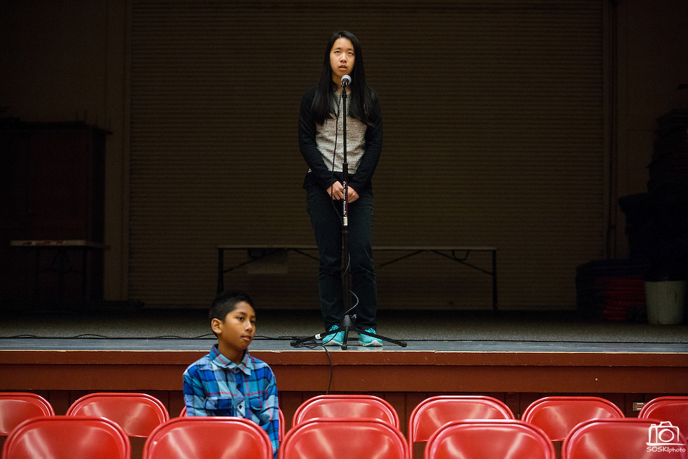 Seventh grader Jaz Reyes, blue, looks on as eighth grader Vanessa Cho spells a word during the final round of the 1st Annual Spelling Bee at Rancho Middle School in Milpitas, California, on December 9, 2015. (Stan Olszewski/SOSKIphoto)