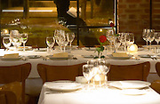 View over the restaurant dining room, tables set for dinner guest with white plate, linen napkin with black rose, silverware knives and forks, spoons wine glasses. The Rosa Negra Restaurant, The Black Rose, Buenos Aires Argentina, South America