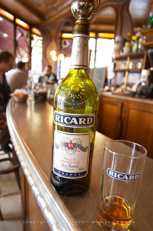 A bottle of Ricard 45 pastis and a glass on a zinc bar in a cafe bar in Paris. In the background people sitting at the bar and bottles on shelves. Pastis is a spirit high alcohol drink flavoured flavored with herbs such as anise (badiane, anis étoilé etoile) and other spices. It is sometimes called pastis or Absinth absinthe. It is served in a tall glass with ice and you pour water on it. It gets cloudy milky when water is added. It is a favourite drink aperitif in Provence Southern France. The Bistrot du Peintre is an old fashioned Paris café cafe bar restaurant of art nouveau design with polished brass, mirrors and old signs