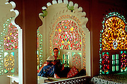INDIA, RAJASTHAN Udaipur; a young woman in the Maharani's  Suite of the famous Lake Palace Hotel on  Lake Pichola