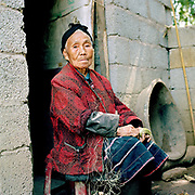 """An elderly Bai Xing style Miao woman sits outside her home splicing ramie fibre, Lao Zhai Zi village, Guizhou province, China. Ramie is one of the oldest fibre crops, having been used for at least six thousand years, and is principally used for fabric production. It is a bast fibre and the part used is the bark of the vegetative stalks. Almost 35% of Guizhou's population is made up of over 18 different ethnic minorities including the Miao. Each Miao group became isolated in these mountainous regions, hence the present day diversity in their culture, costume and dialects. According to a popular saying, """"if you meet 100 Miaos, you will see 100 costumes."""""""