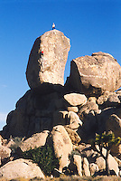 Two men rock climbing on a giant boulder.  Joshua Tree National Park, California, USA.  Headstone Boulder.  Route Difficulty is 5.7.<br />