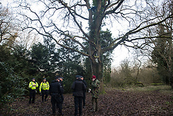 Denham, UK. 3 February, 2020. Police officers monitor environmental activists from Extinction Rebellion, Save Colne Valley and Stop HS2 who are seeking to prevent works for the HS2 high-speed rail link including the felling of 200 trees and the construction of a Bailey bridge, compounds, fencing and a parking area. Part of the location for the work lies within a wetland nature reserve forming part of a Site of Metropolitan Importance for Nature Conservation (SMI). In spite of a substantial police presence, HS2 were not able to proceed with the work for the day.