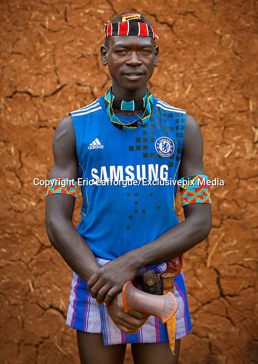 The football stars of tomorrow<br /> <br /> Thousands of Football shirts of Arsenal, Manchester, Chelsea, Milano, etc end up their carreer in... Ethiopia. Sold in the deep south, in the Omo Valley, those second hand clothes are bought by the local tribes. Most of them ignore the meaning of those shirts, and just buy them for the color, the logo, or the shape.<br /> No warrior will go out without his little pillow/seat.<br /> Some, like in Hamer tribe wear at the top of the head a clay helmet where they can put some ostrich feathers when they make a special action, like killing a wild animal, or...a man.<br /> Those tribes won't exist in few years as the ethiopian governement has launched a huge plan to develop the area.<br /> Soon, a highway coming from Mombassa - Nairobi will pass thru the villages to reach Addis Ababa.<br /> <br /> Photo shows: Bana tribe- Chelsea FC<br /> ©Eric Lafforgue/Exclusivepix Media
