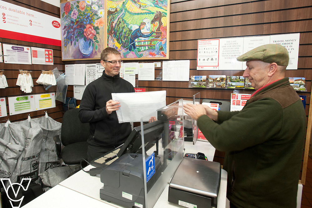 Pictured is postmaster Dave Bray serving customer Paul Robinson<br /> <br /> Barley Post Office, Church End, Royston, Hertfordshire.<br /> Date: January 23, 2015