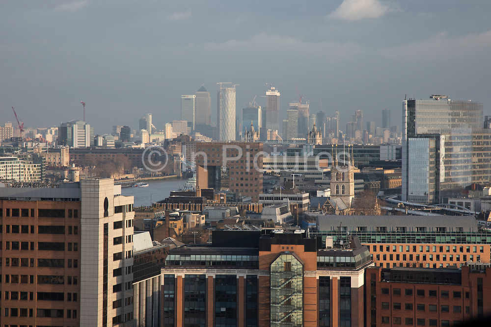 Cityscape skyline view over rooftops and River Thames over Southwark and London Bridge towards the financial district and skyscrapers at Canary Wharf in London, England, United Kingdom.