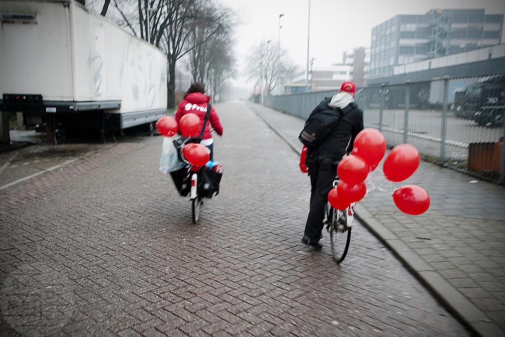 Leden van de PvdA gaan op weg met ballonnen op de fiets om campagne te voeren voor de verkiezingen van de provinciale staten.<br /> <br /> Members of the Dutch labour party PvdA are cycling with balloons on their bikes to go on campaign for the next elections.