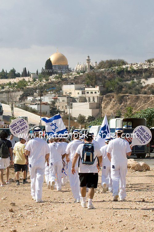 Israel, Jerusalem, People marching in the Jerusalem annual parade Dome of the rock in the background October 2009